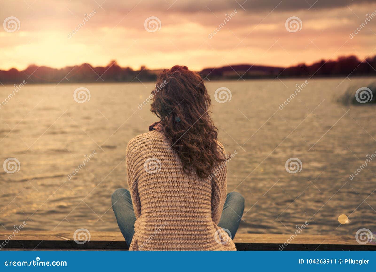 Kobieta siedzi przy jeziorem