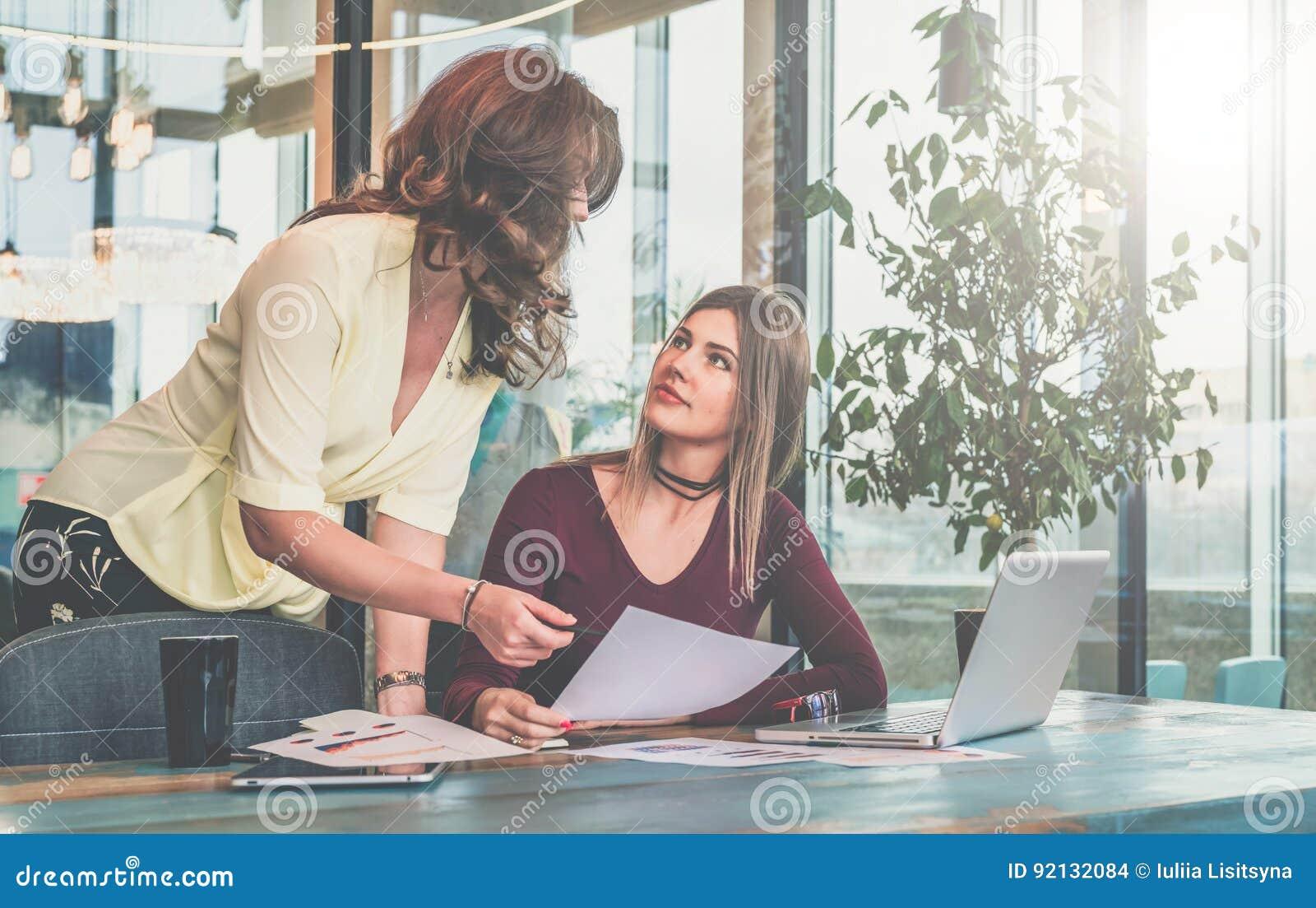 Kobieta siedzi w biurze przy stołem przed komputerem i chwytów dokumenty w jej ręce, po drugie stoją obok ona