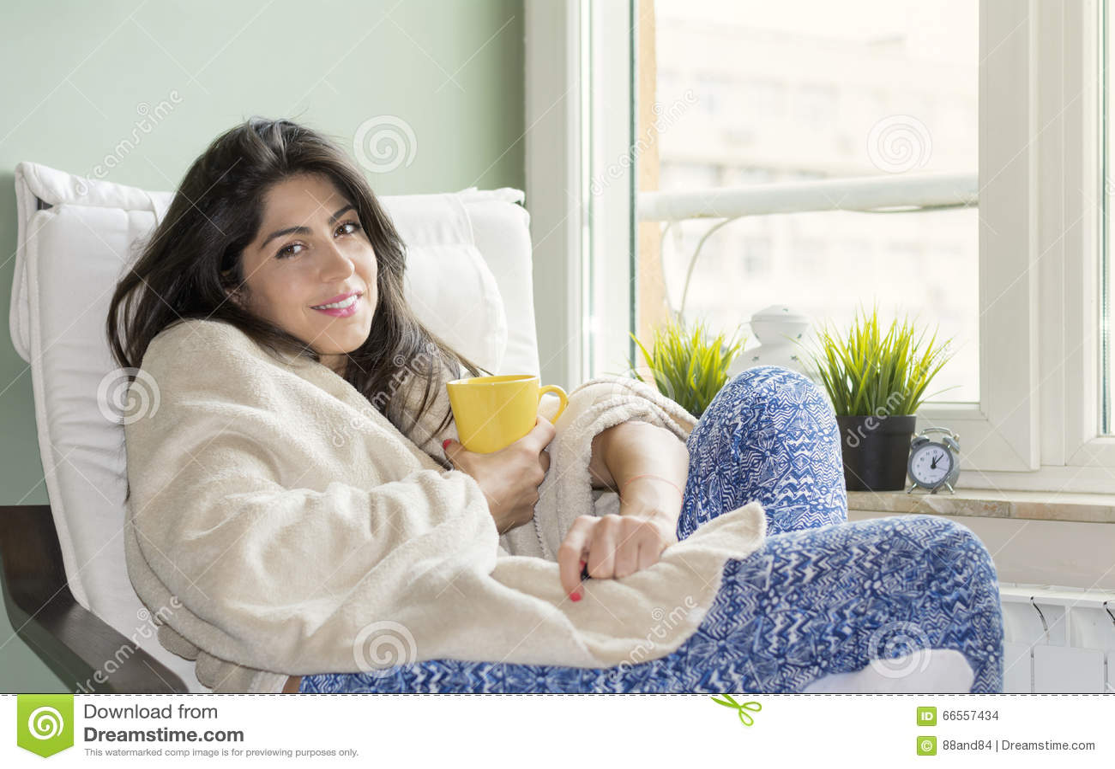 Kobieta siedzi w domu, zawijający w powszechnym, pijący herbaty