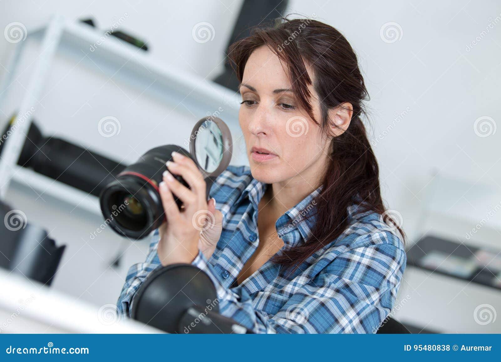Kobieta sprawdza kamery lense używać powiększać - szkło