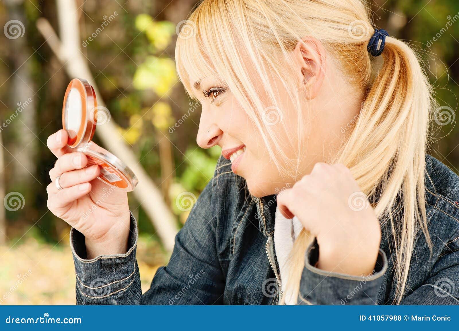 Kobieta sprawdza włosy w lustrze