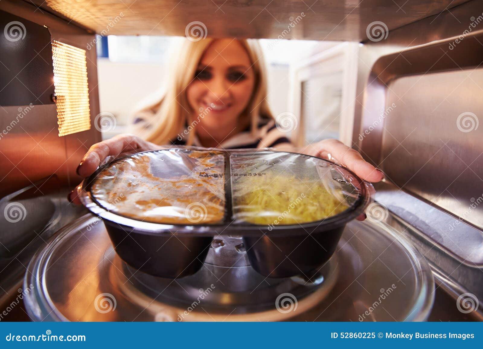 Kobieta Stawia TV gościa restauracji W mikrofala piekarnika Gotować