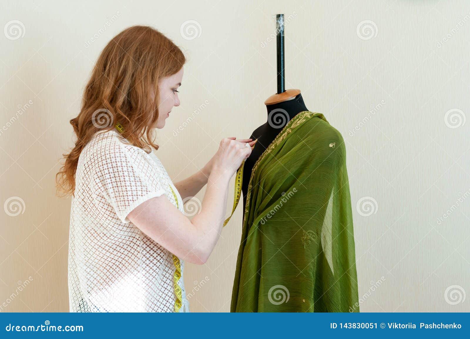 Kobieta stoi blisko czarnego mannequin i stawia płótno