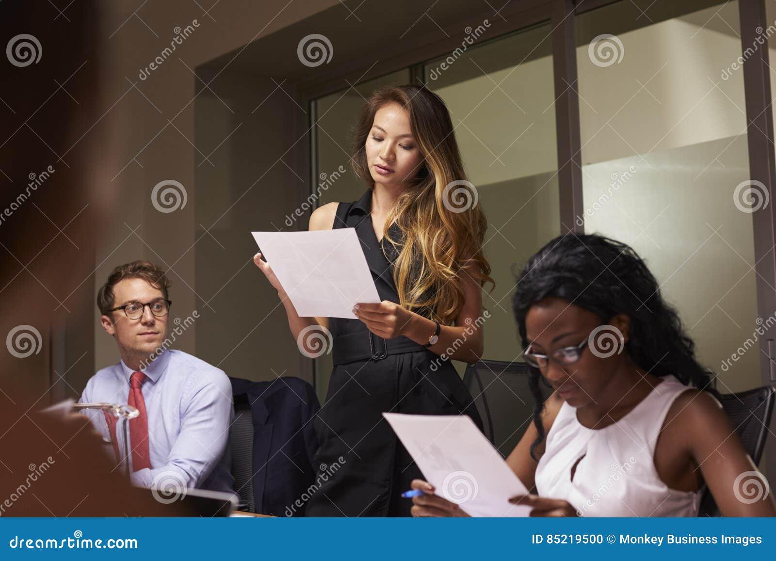 Kobieta stoi czytanie dokument przy wieczór biznesowym spotkaniem