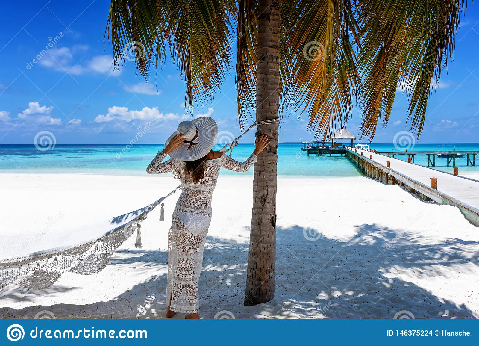 Kobieta stojaki na tropikalnym raju wyrzucać na brzeg w Maldives