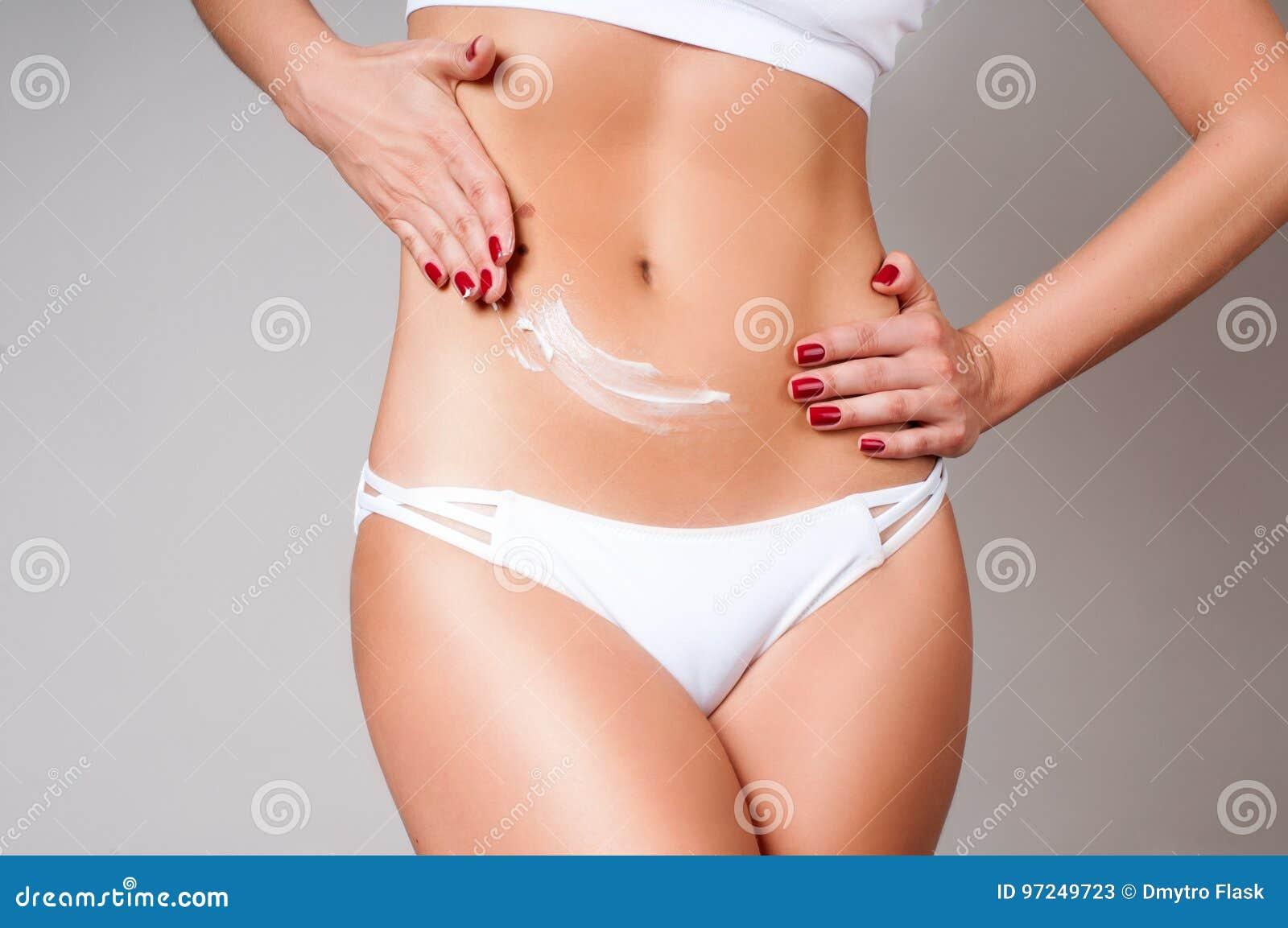 Kobieta stosuje moisturizer kremową płukankę na brzuchu Kobiety odzieży bielu bielizna
