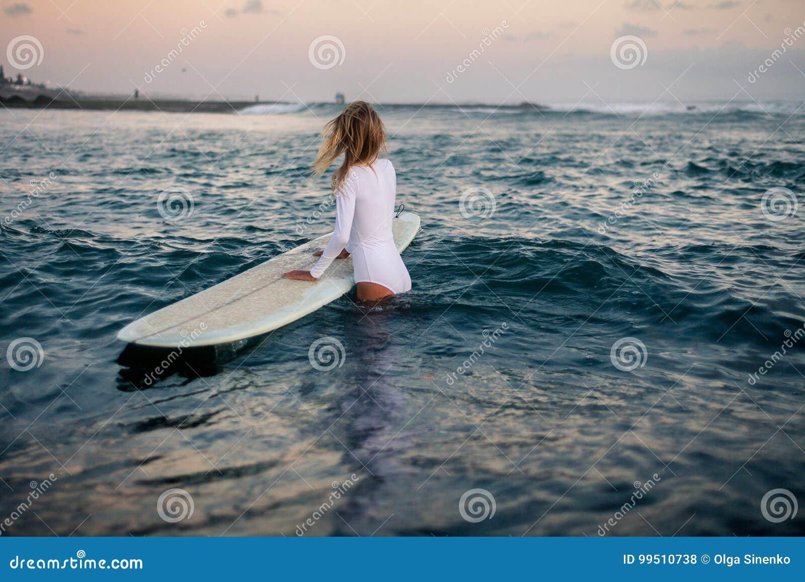 Kobieta surfingowiec z deską w rękach przy plażą