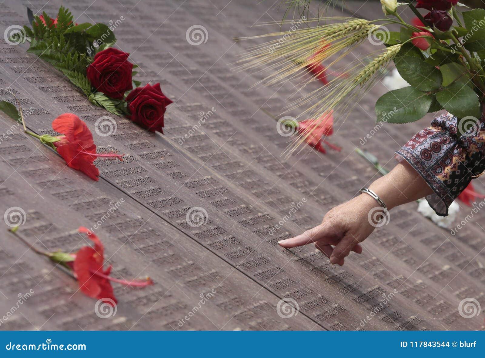 Kobieta szukał imię jej krewni w pamięci ściany pamiątkowym grób w Mallorca