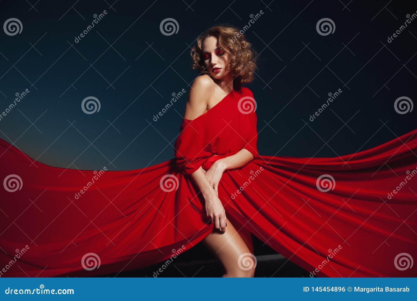 Kobieta taniec w jedwab sukni, artystycznym czerwonym podmuchowym togi falowaniu i lata tkaninie,