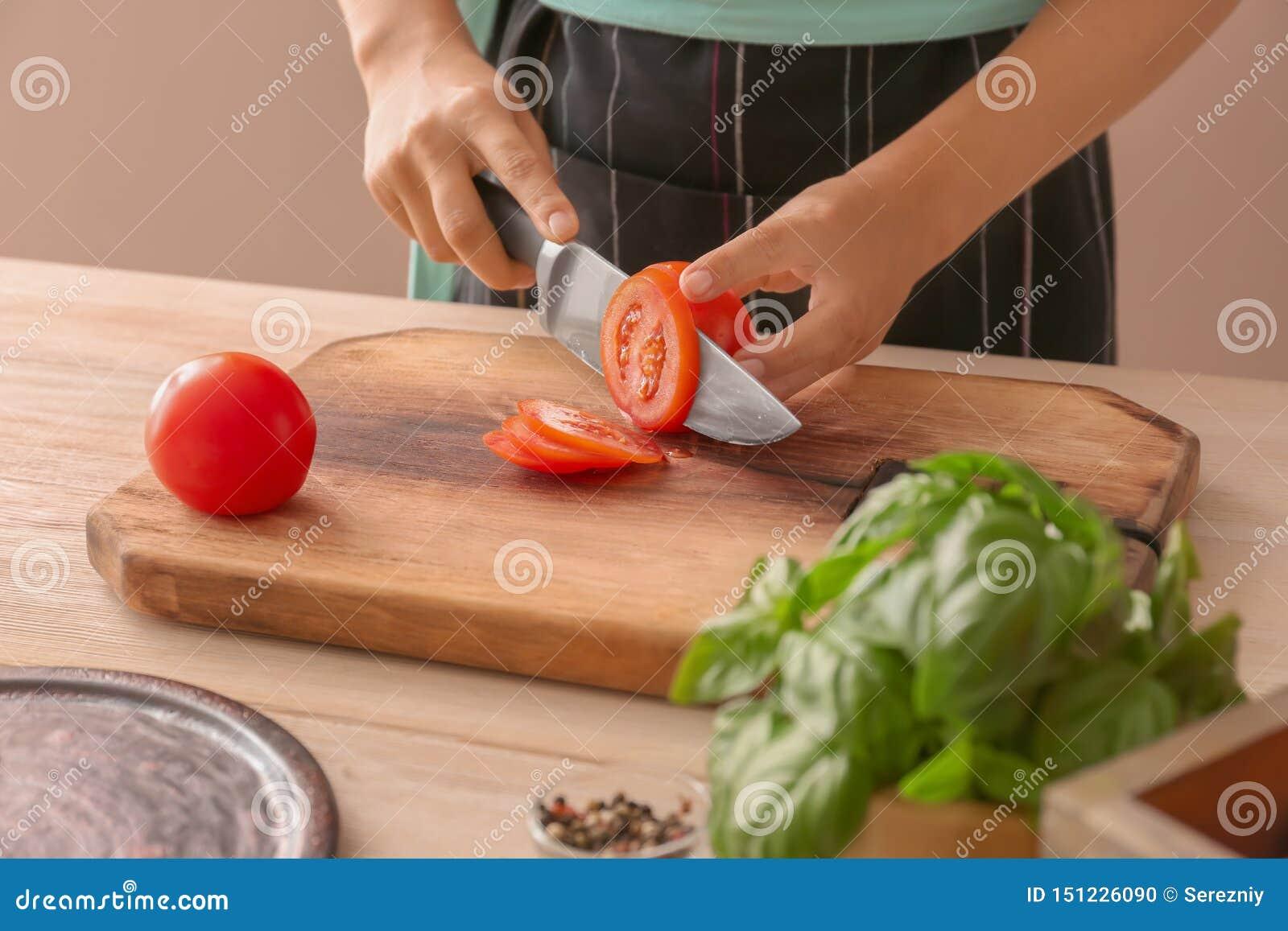 Kobieta tnący pomidor na drewnianej desce, zbliżenie