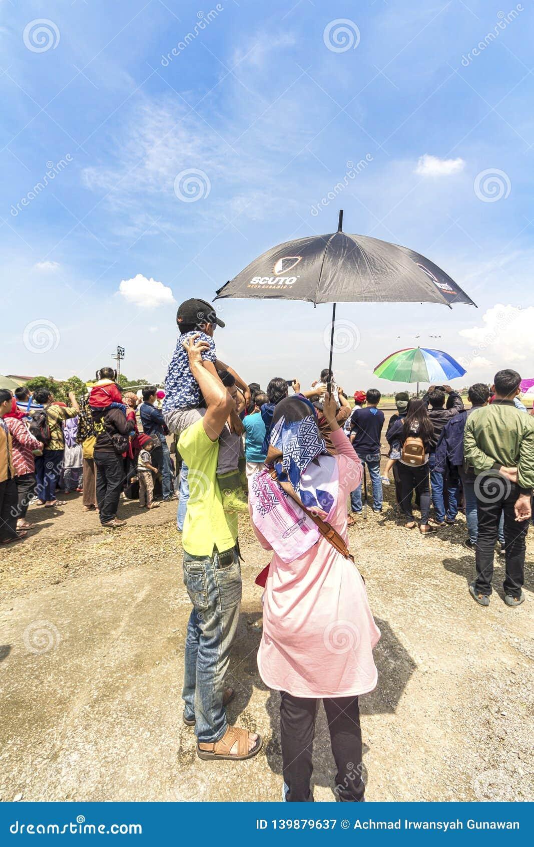 Kobieta trzymał parasol dla jej syna i męża podczas gdy oglądający aerobatic przedstawienie przy Bandung pokazem lotniczym 2017