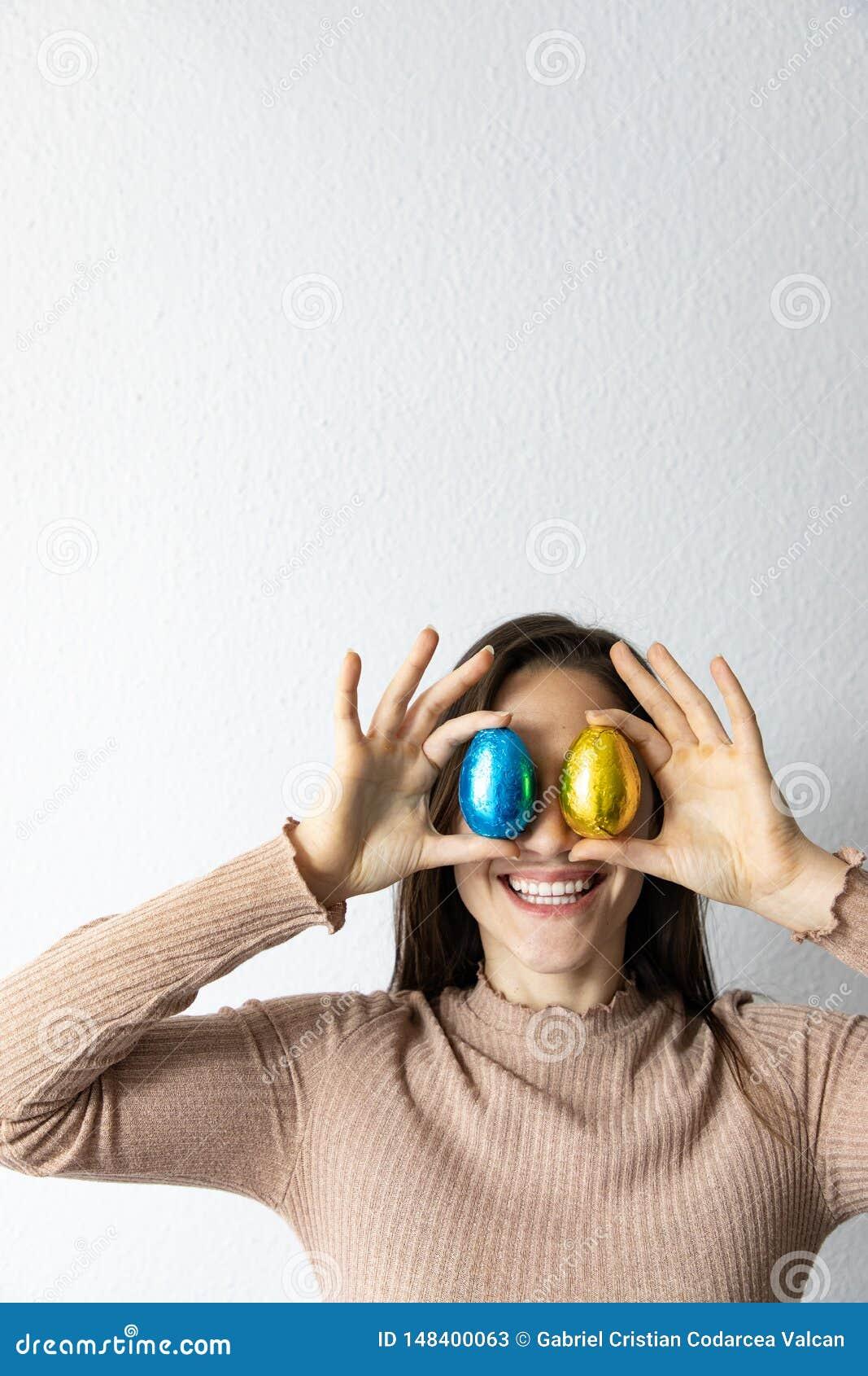 Kobieta trzyma b??kitnych i z?otych czekoladowych Easter jajka przed jej oczami