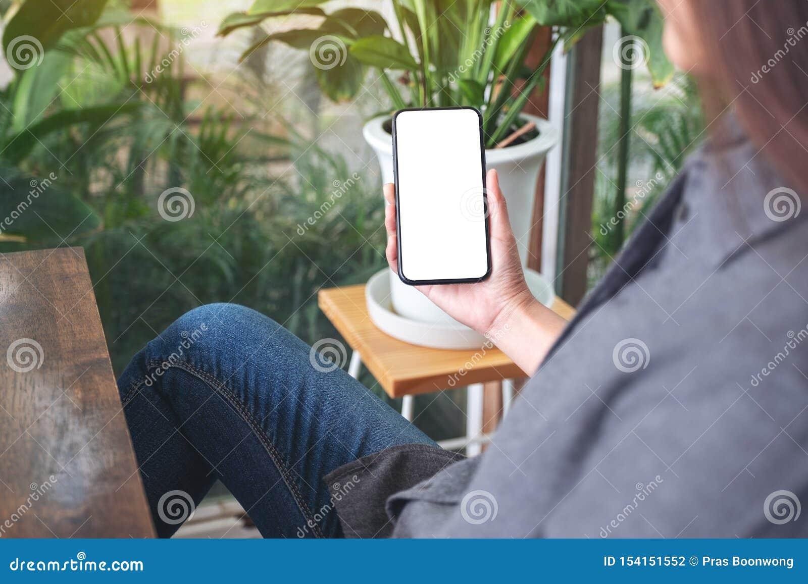 Kobieta trzyma czarnego telefon komórkowego z pustym desktop ekranem i używa w kawiarni