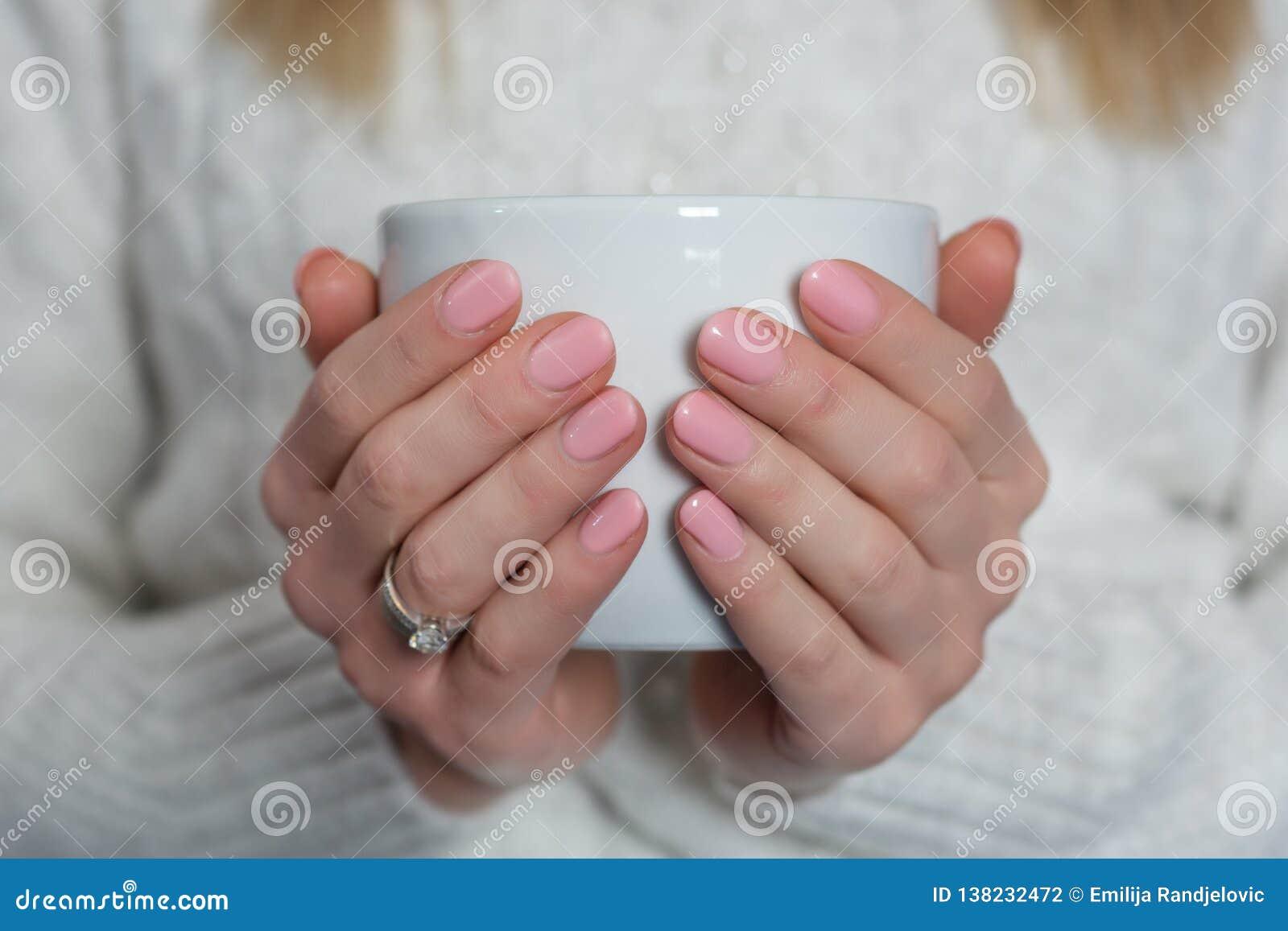 Kobieta trzyma filiżankę herbata z dziecko menchiami barwi gwoździa połysku gel na palcach