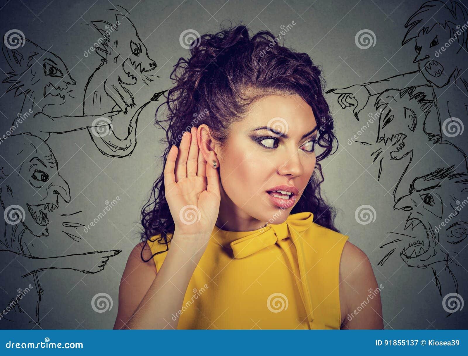 Kobieta trzyma jej rękę blisko ucho i słucha ostrożnie zli głosy