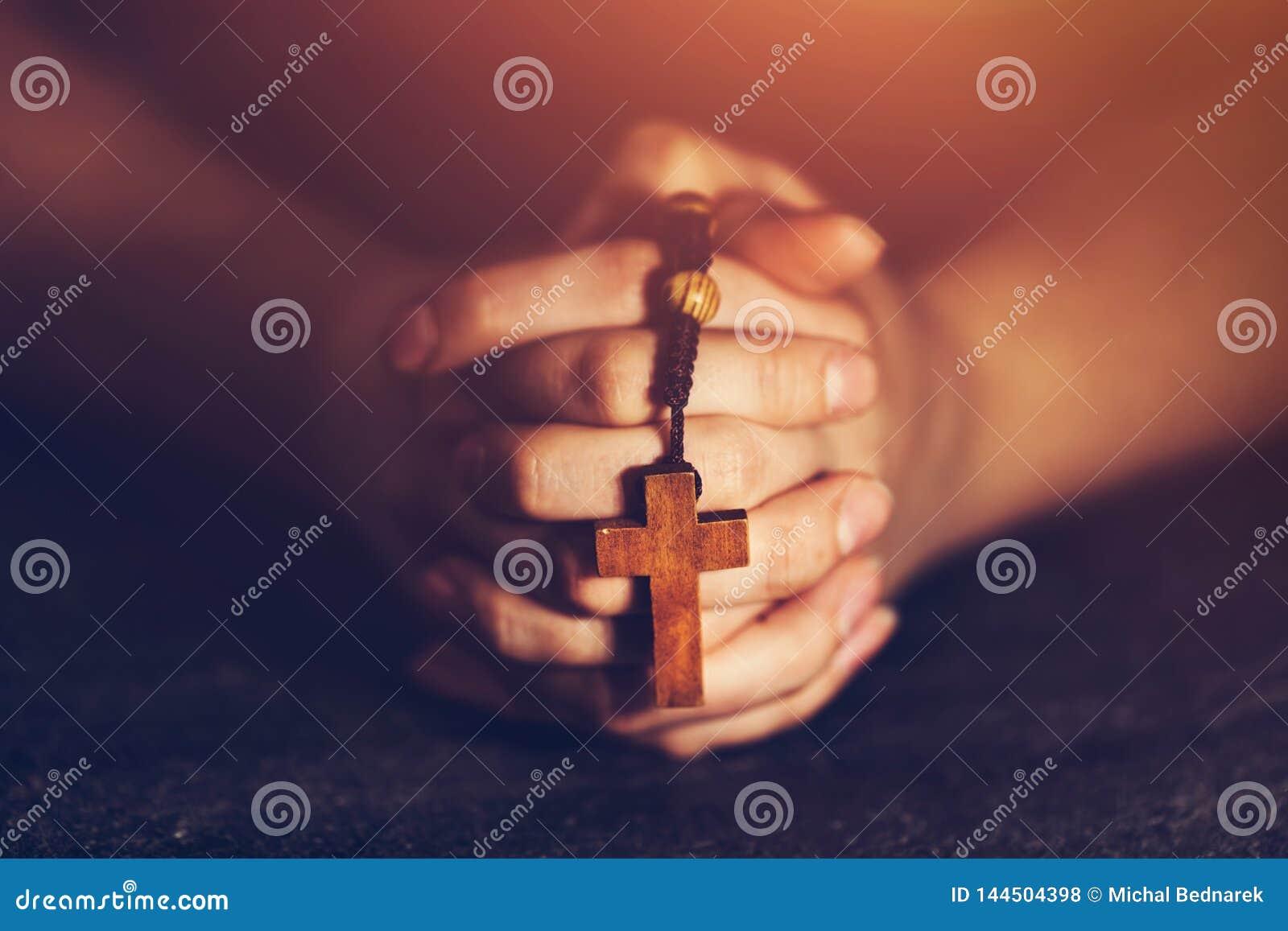 Kobieta trzyma ono modli się i różana
