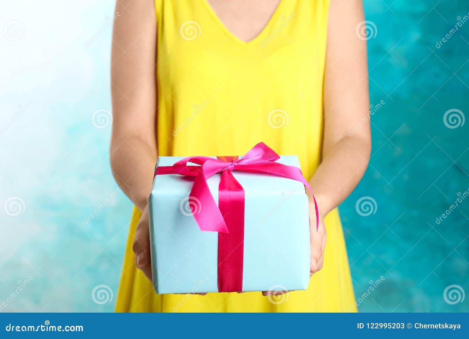 Kobieta trzyma pięknie zawijającego prezenta pudełko na koloru tle