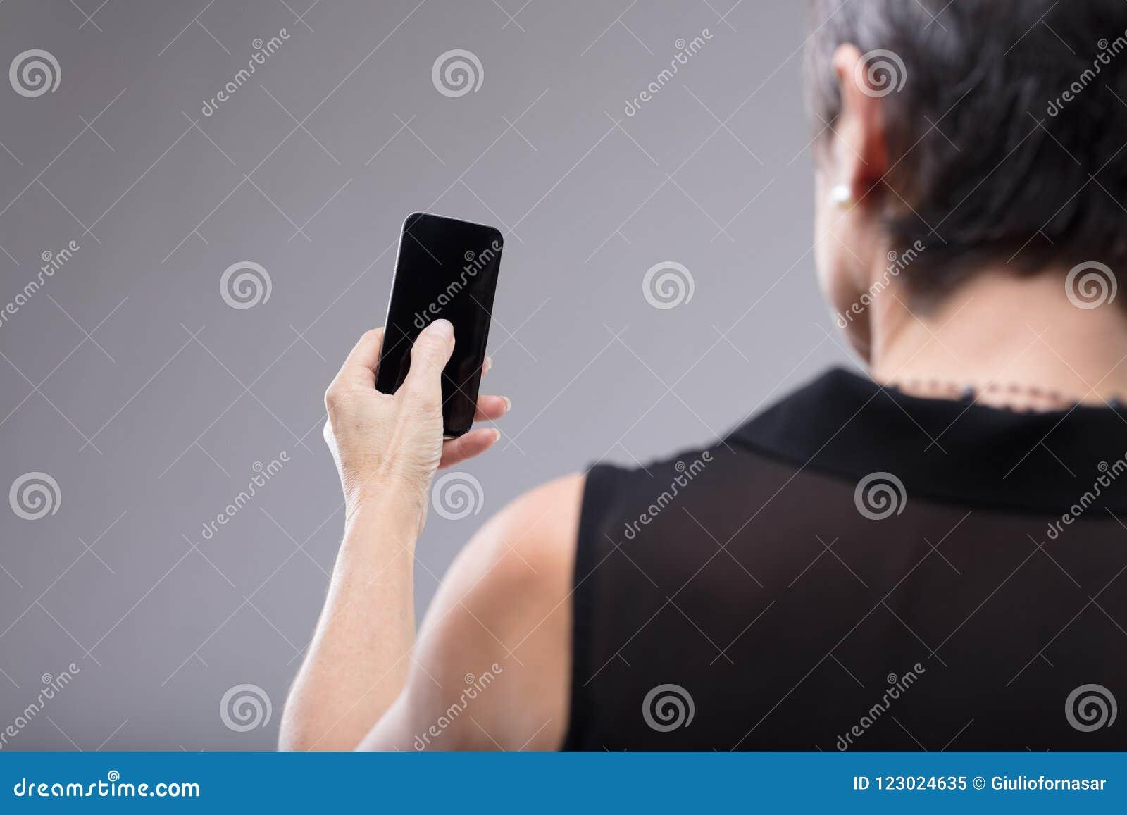 Kobieta trzyma pustego czarnego telefon komórkowego