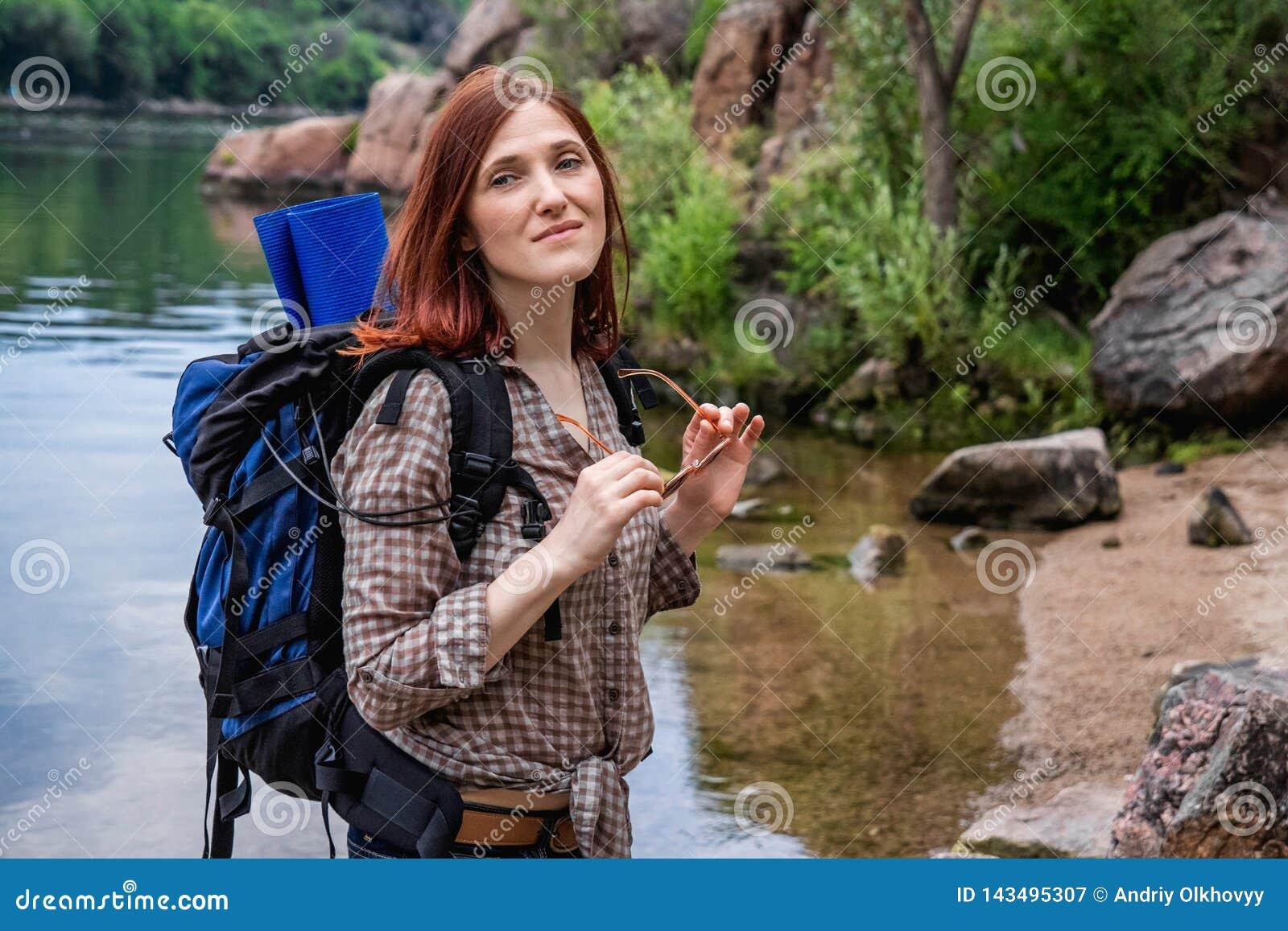 Kobieta turysta z plecaka spacerem w podwyżce przeciw tłu piękna halna sceneria wzdłuż halnej rzeki