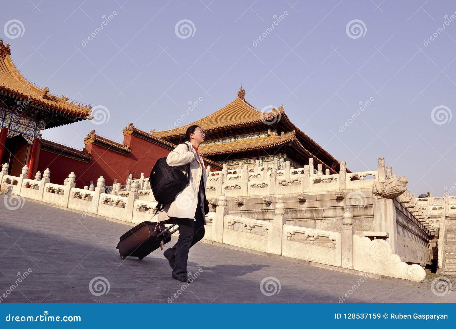Kobieta turysta z walizką przy Niedozwolonym miastem, Chiny