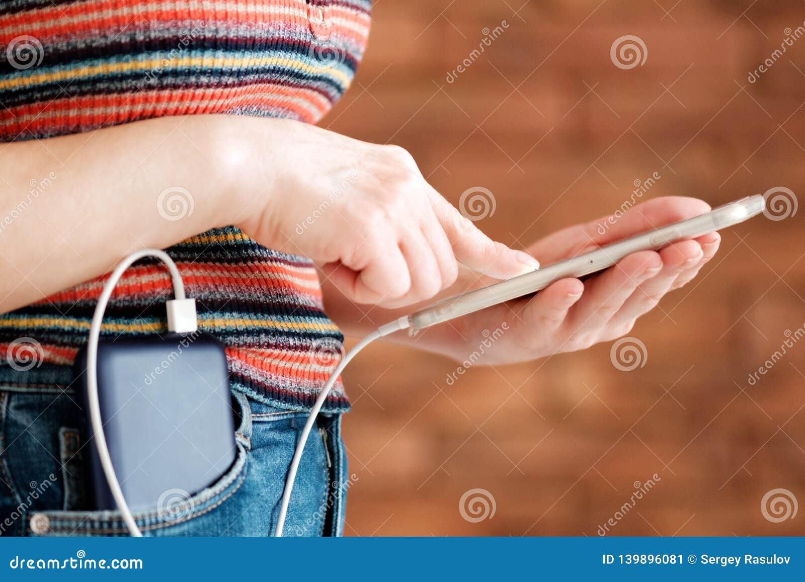 Kobieta używa mądrze telefon podczas gdy ładować na władza banku