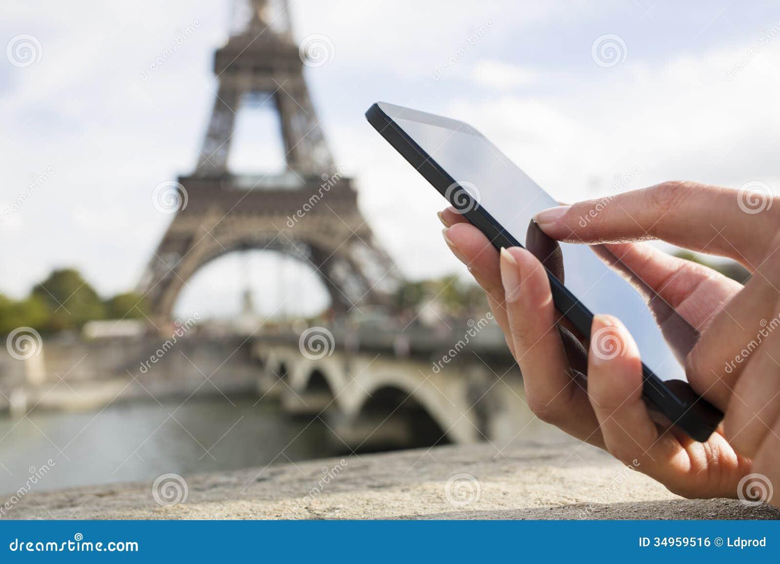 Kobieta używa jej telefon komórkowego przed wieżą eifla