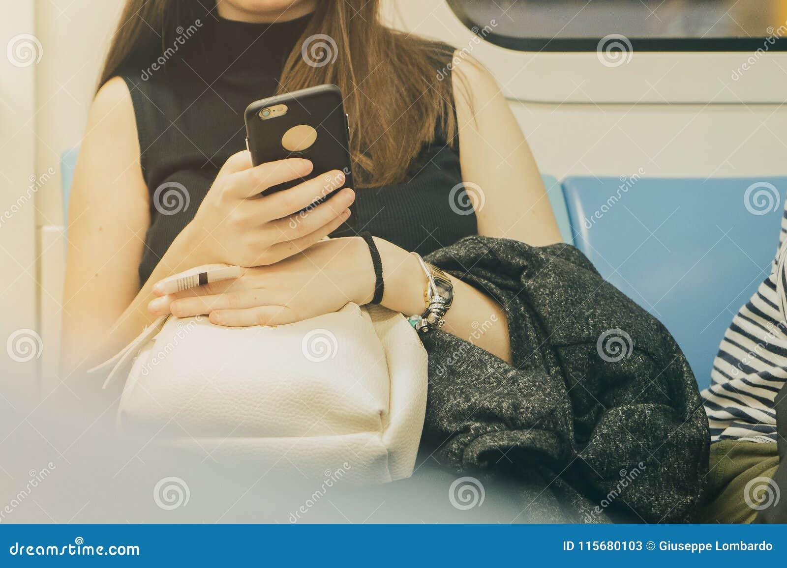 Kobieta używa jej telefon komórkowego w metrze