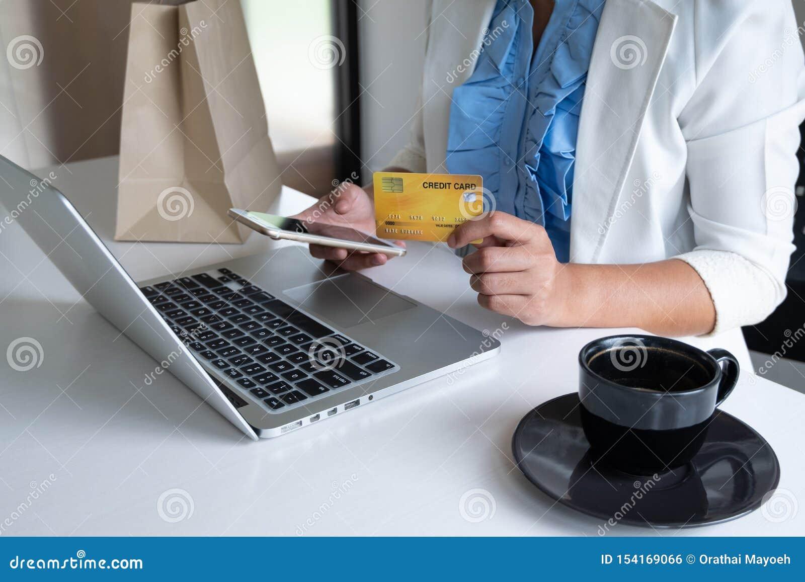 Kobieta używa kartę kredytową dla online zakupy na jej telefonie i laptopie