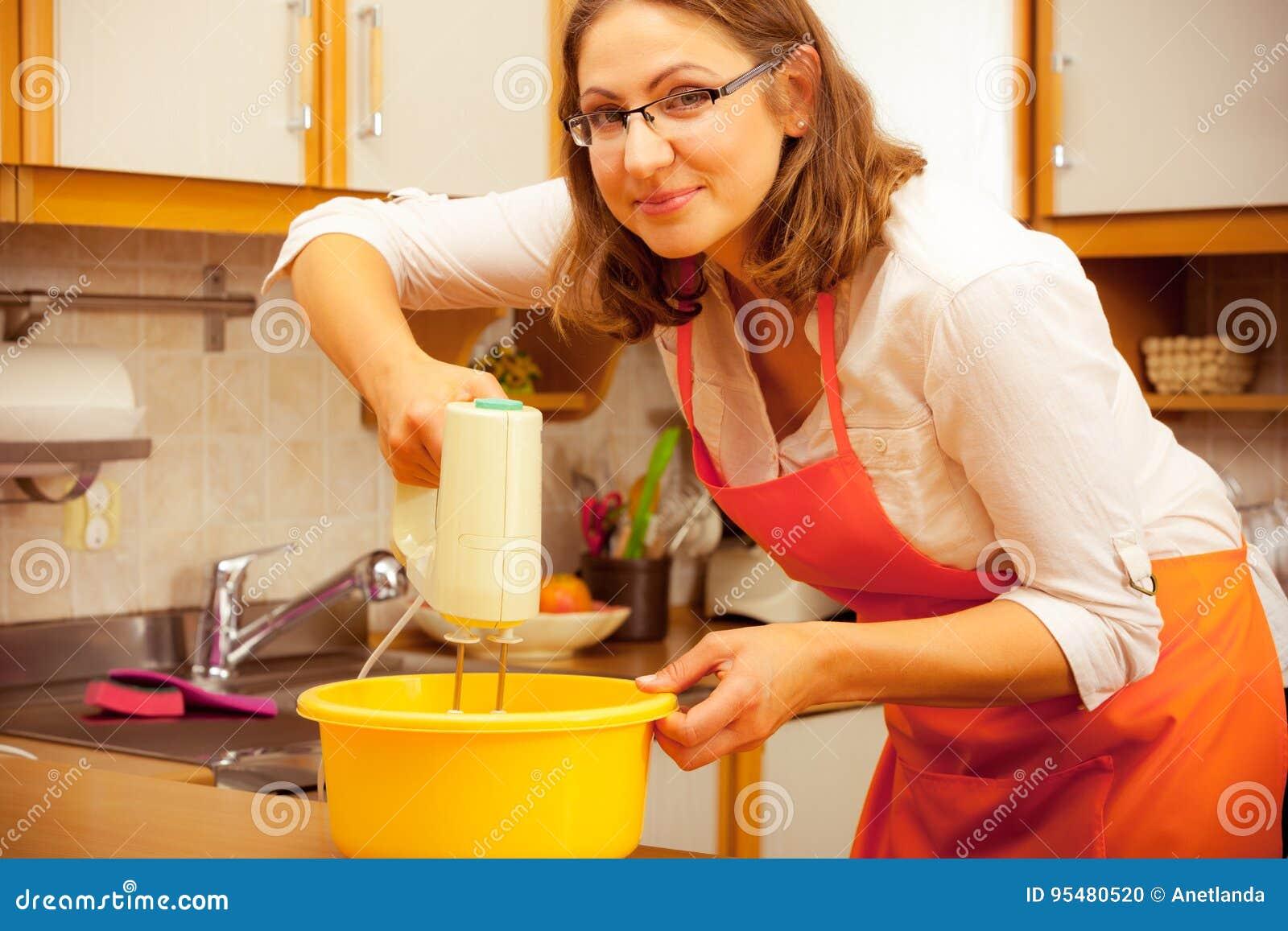 Kobieta używa melanżer w kuchni