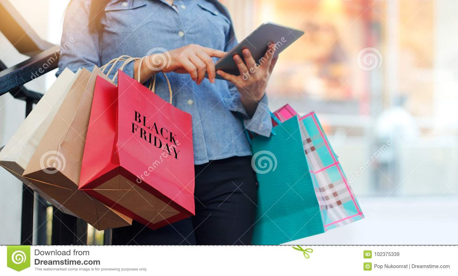 Kobieta używa pastylkę i trzymający Black Friday torba na zakupy