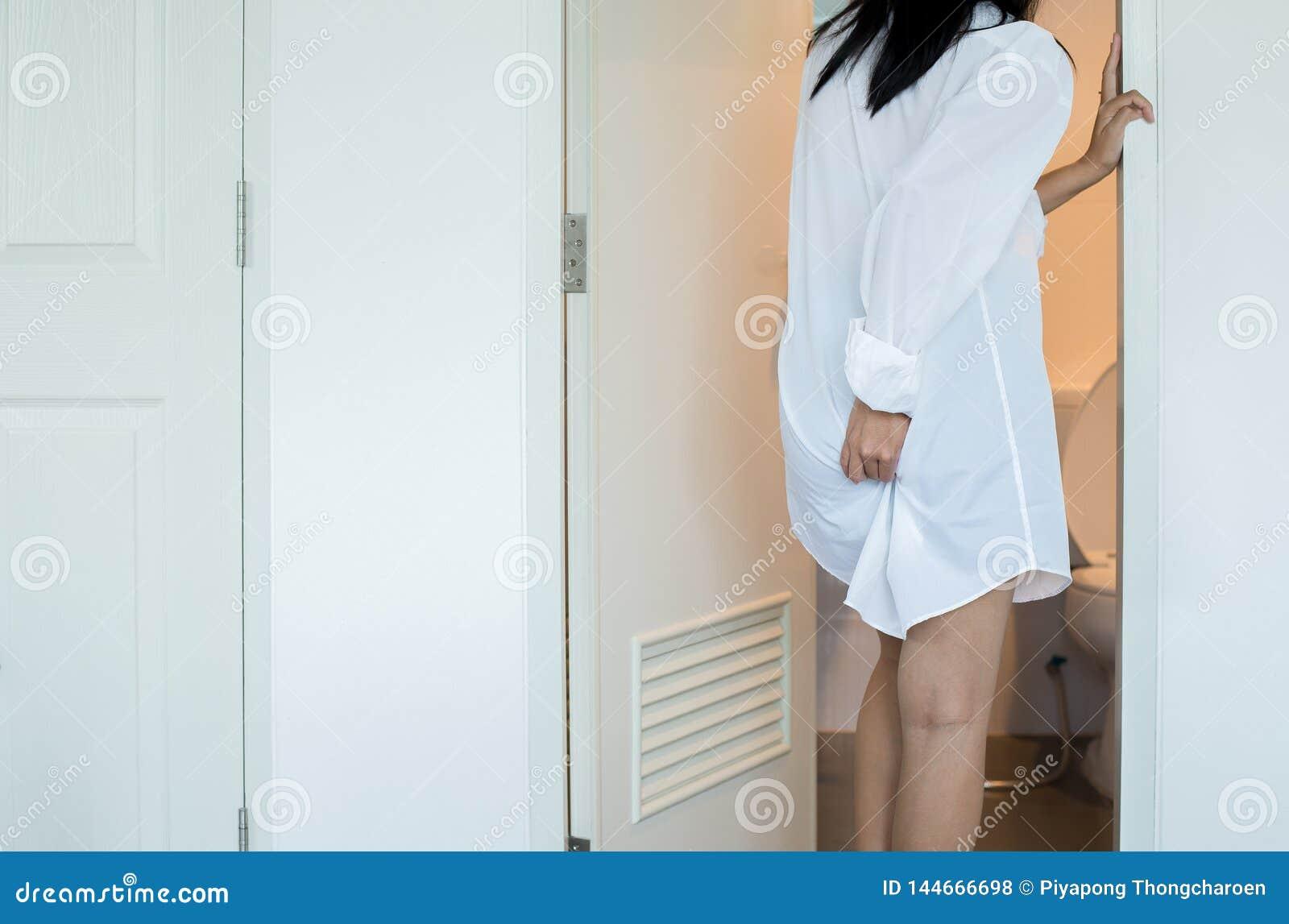 Kobieta używa toaletę i cierpi od biegunki i hemoroidy po budzą się w ranku