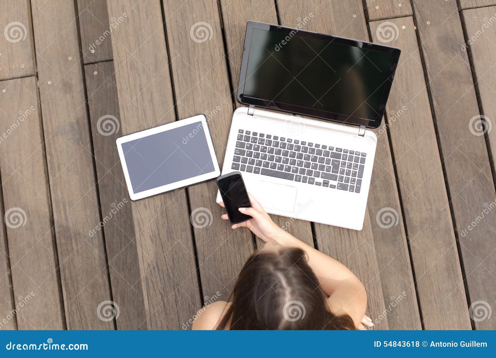 Kobieta używa wieloskładnikowych przyrząda dzwoni laptop i pastylkę