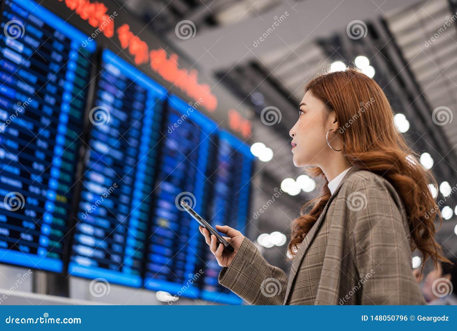 Kobieta u?ywa smartphone z lot informacji desk? przy lotniskiem