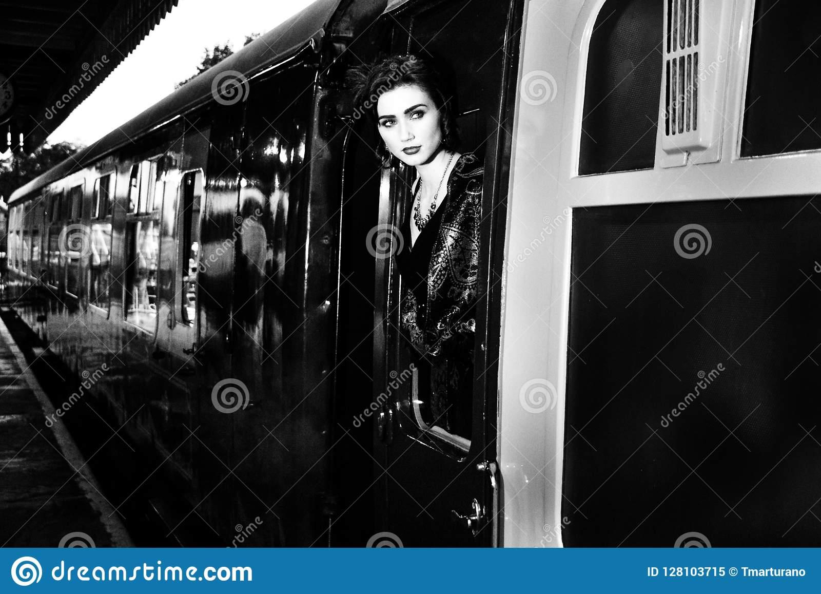 Kobieta ubierał w rocznika wieczór sukni opiera z taborowego okno i dmuchania buziak
