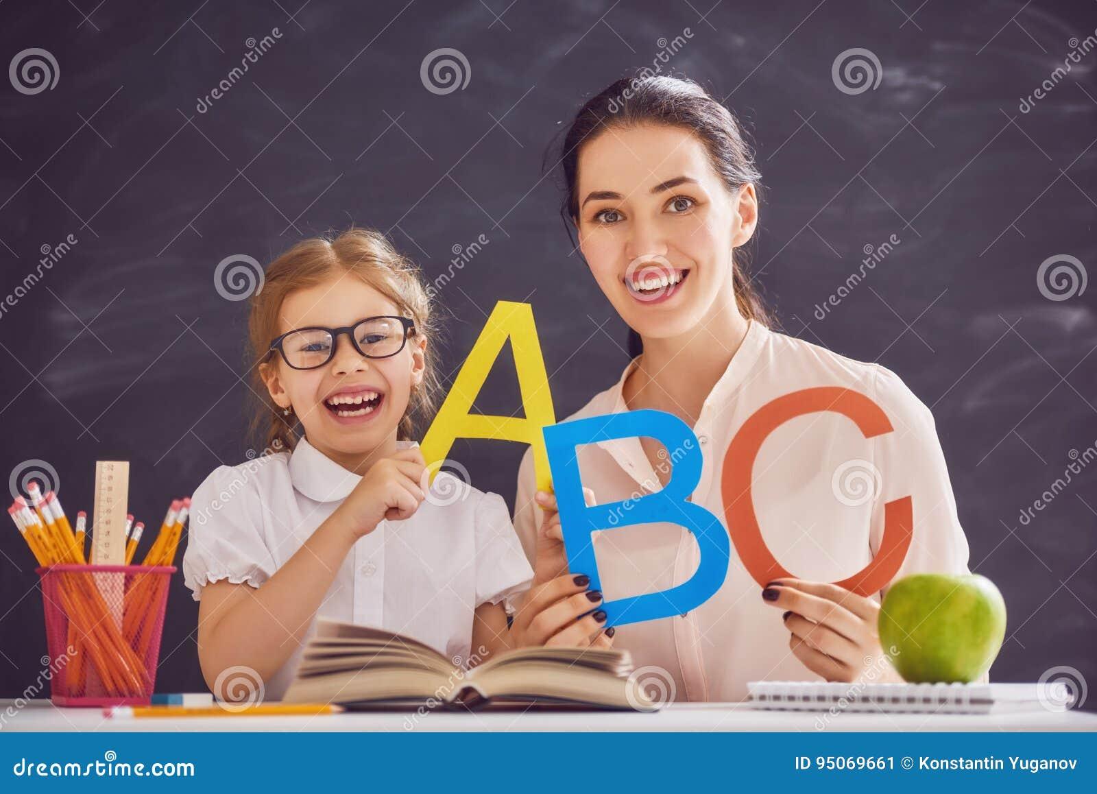 Kobieta uczy dziecku abecadło