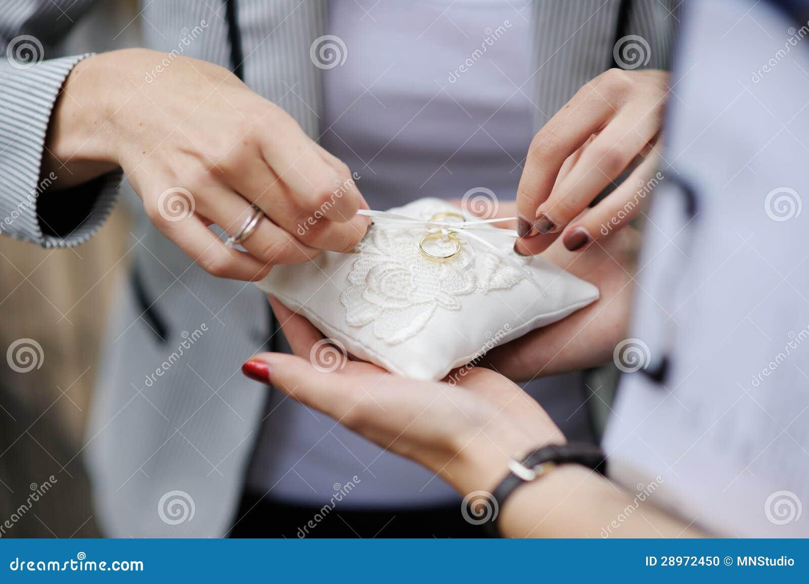 Kobieta umieszcza obrączki ślubne na poduszce