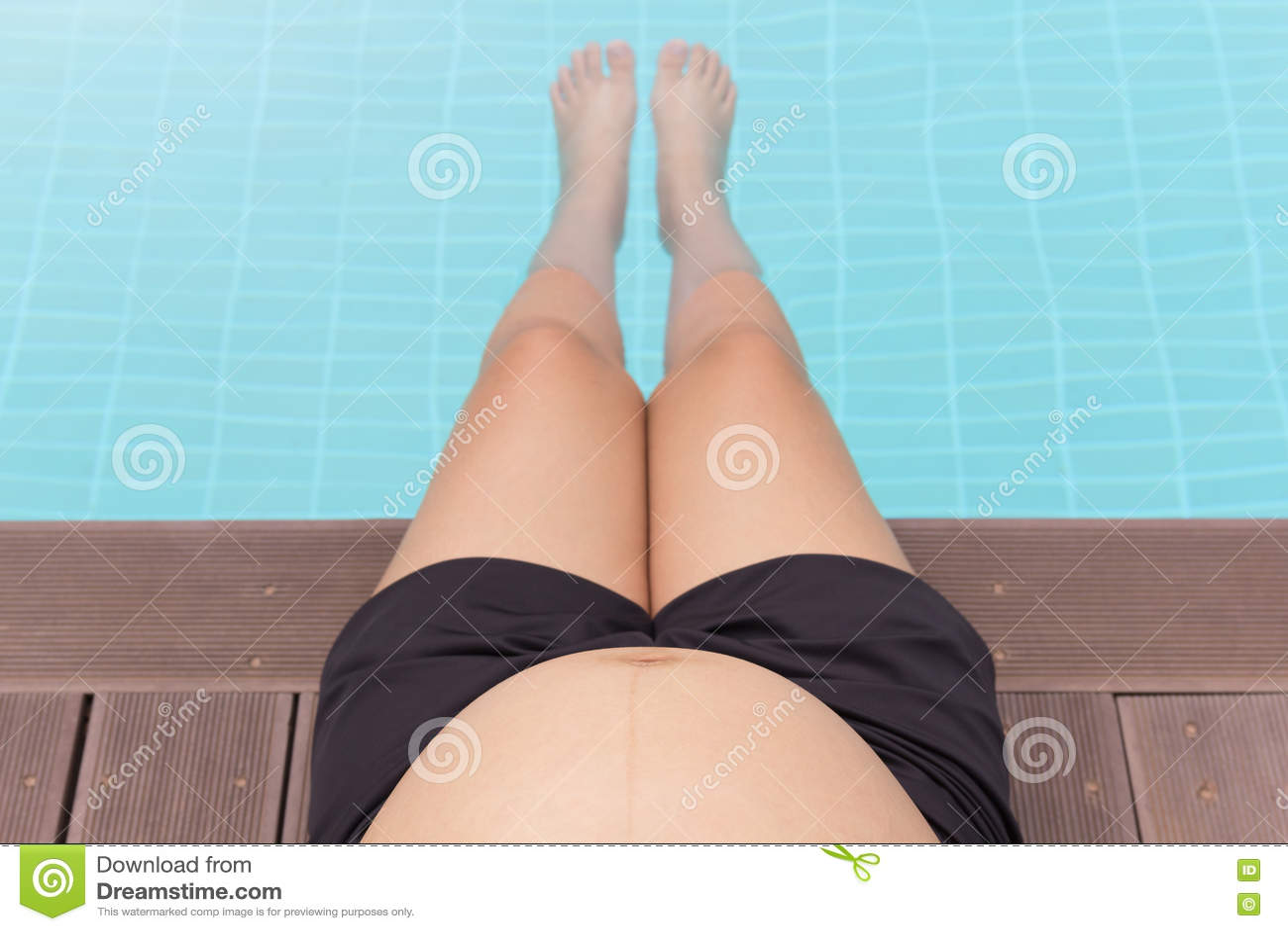 Kobieta w ciąży brzuch z nogami w pływackim basenie
