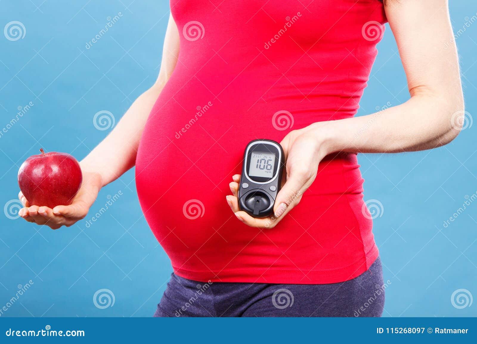 Kobieta w ciąży trzyma świeżego jabłka i glucometer z dobrym rezultata cukieru poziomem, cukrzyce podczas brzemienności