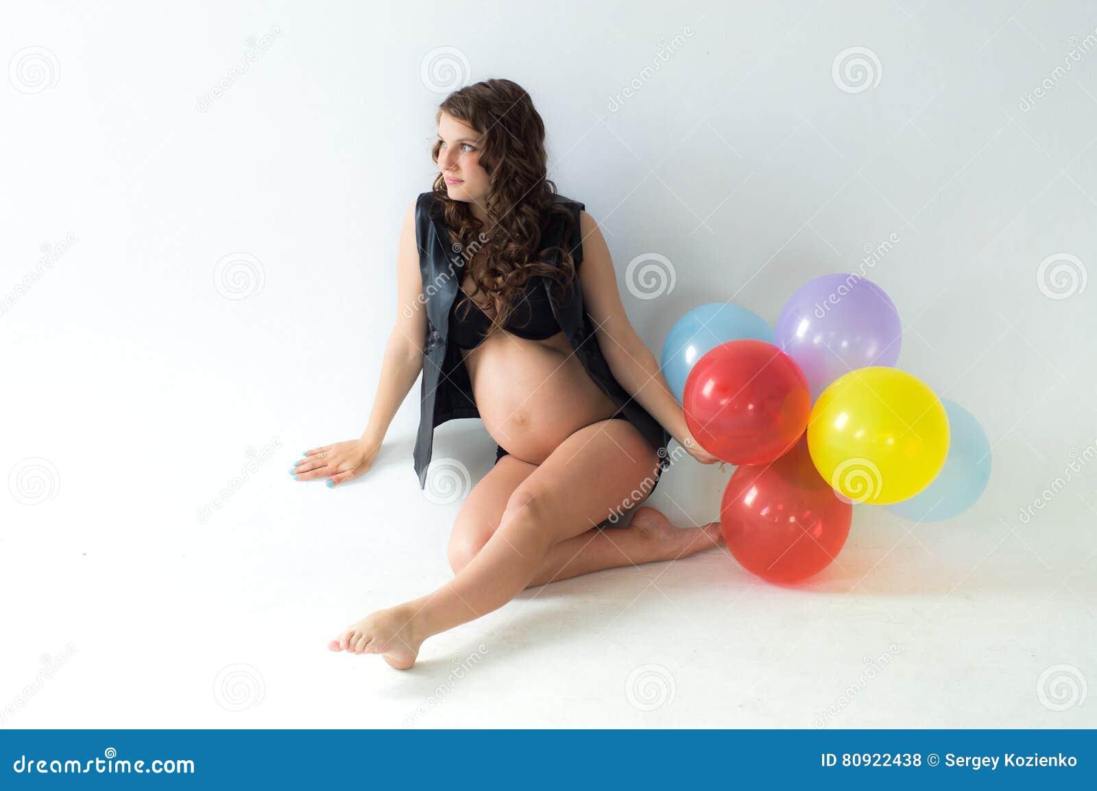 Kobieta w ciąży z balonami siedzi na podłoga