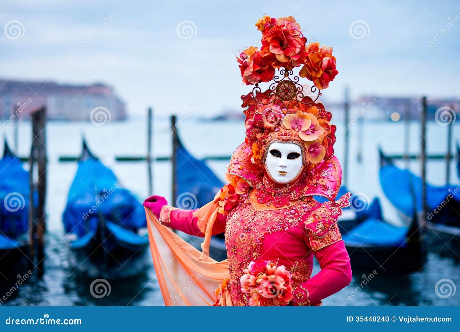 Kobieta w czerwieni sukni maskującej dla Wenecja karnawału przed typowymi gondoli łodziami