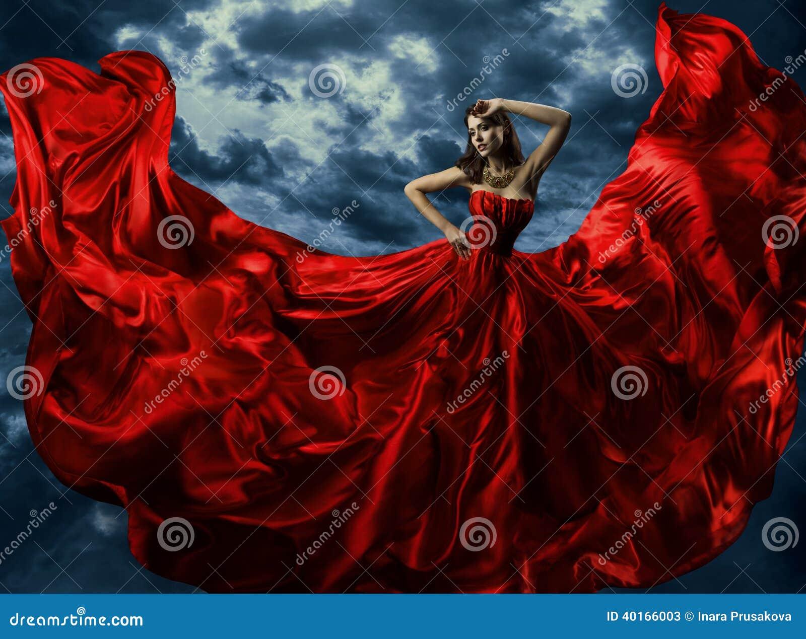 Kobieta w czerwonej wieczór sukni, falowanie toga z lataniem tęsk tkanina