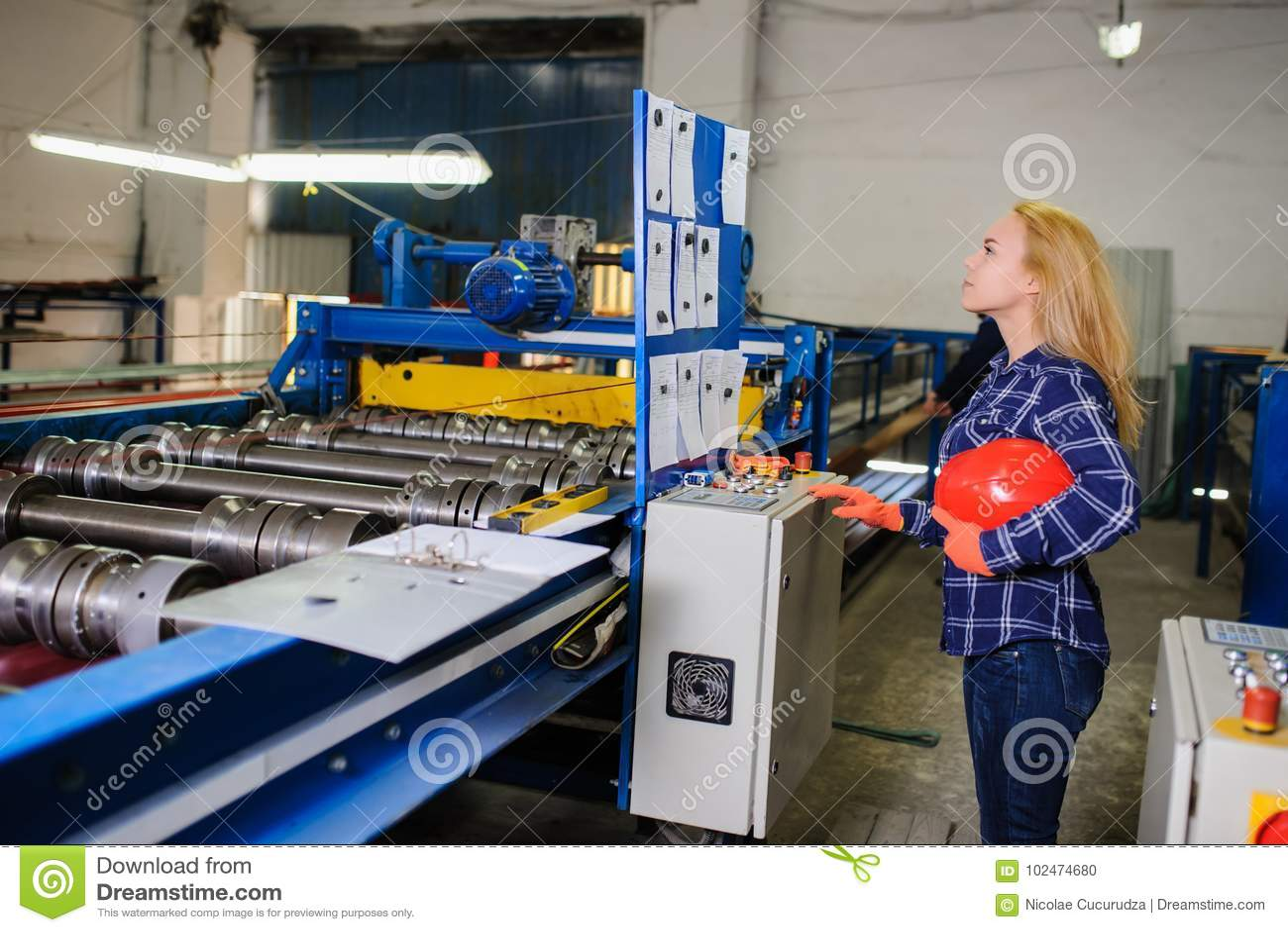 Kobieta w czerwonej zbawczego hełma pracie jako przemysłowy pracownik