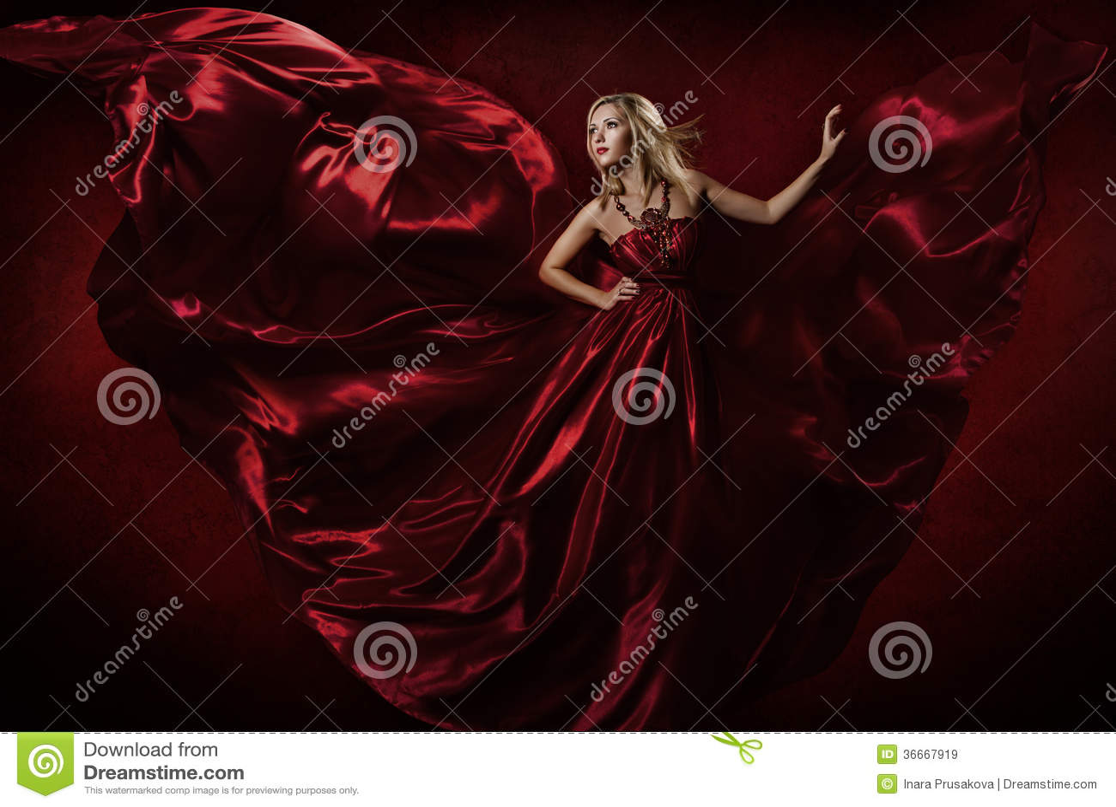 Kobieta w czerwonym falowanie sukni tanu z latającą tkaniną