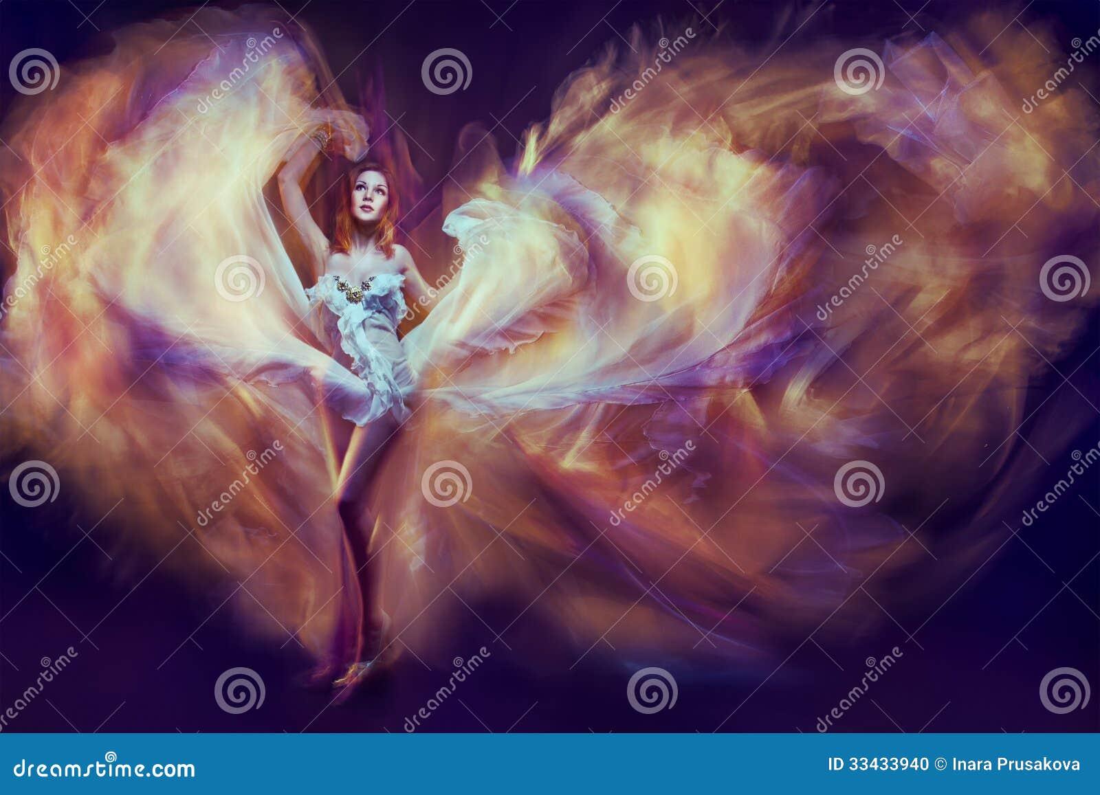 Kobieta w falowanie sukni jako płomienia taniec z latającą tkaniną. Dar