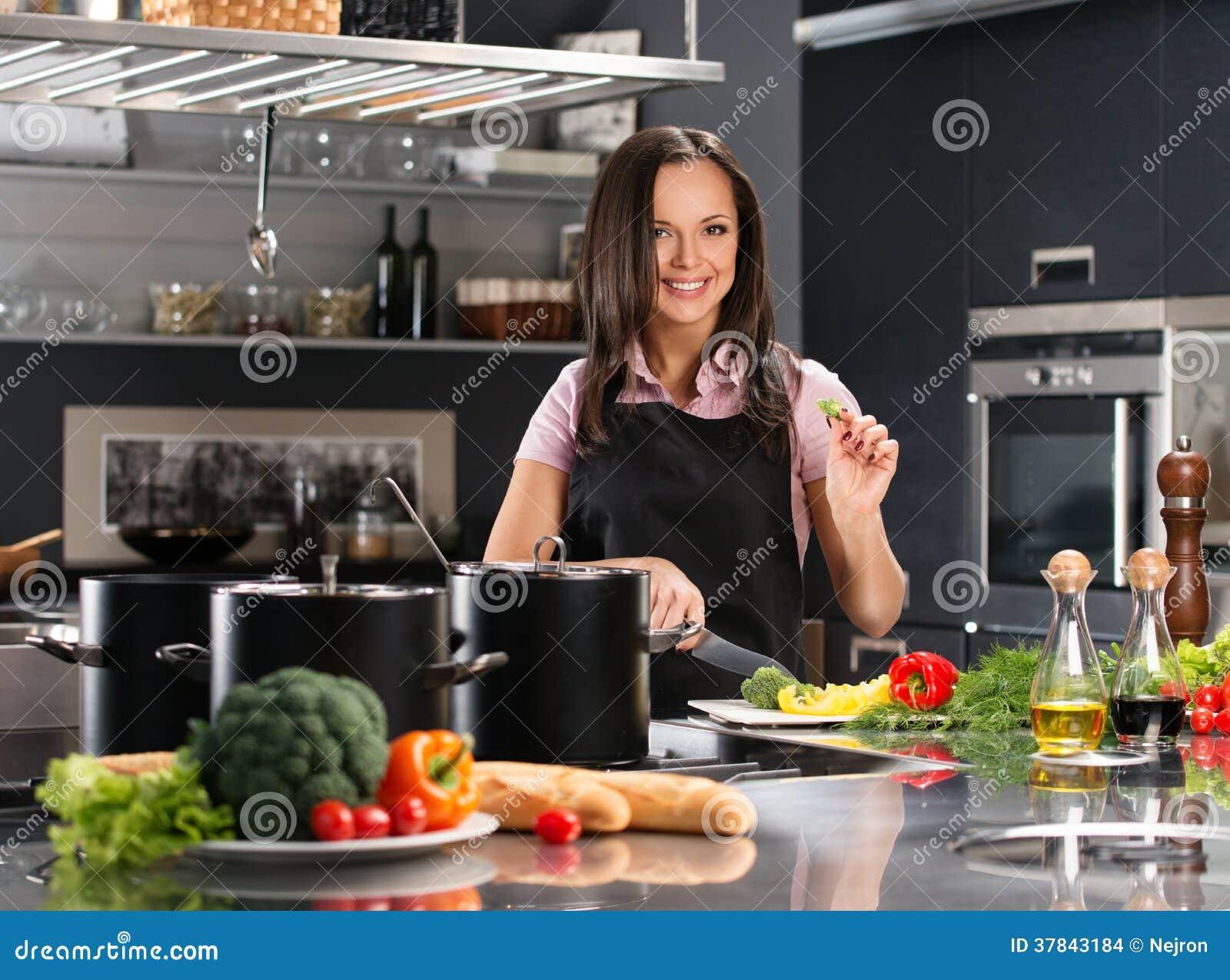 Kobieta w fartuchu na nowożytnej kuchni