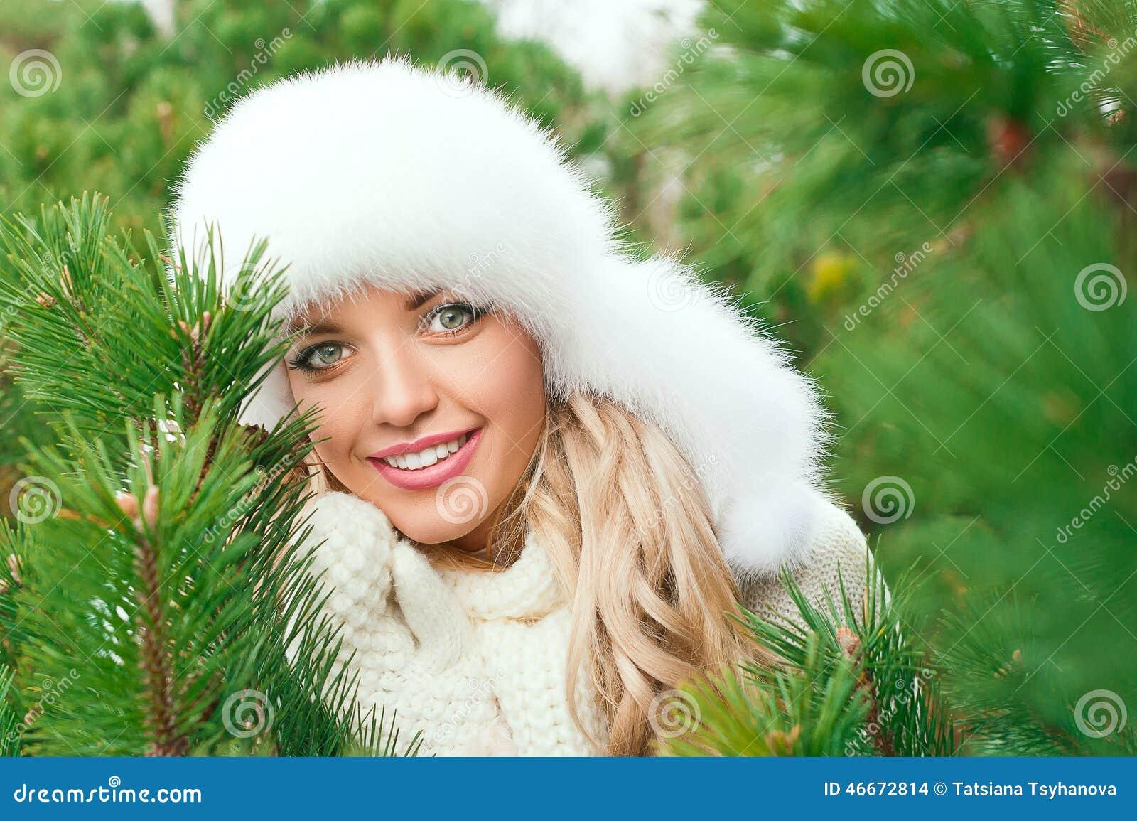 Kobieta w kapeluszu, mitynki, scarves, pulowery, futerko w zimy jodły lesie