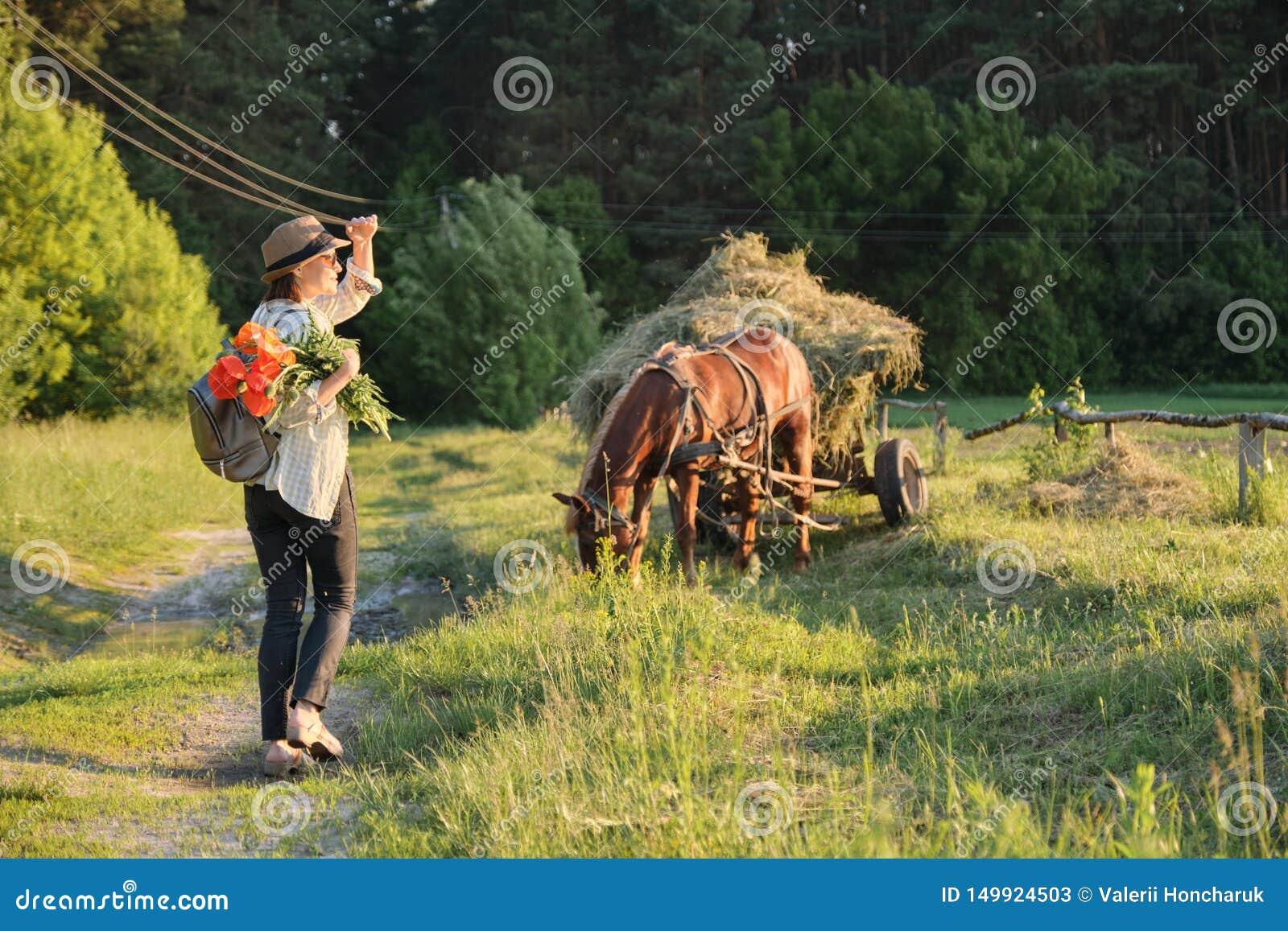 Kobieta w kapeluszu z bukietem czerwoni maczki kwitnie odprowadzenie wzdłuż wiejskiej wiejskiej drogi, tylny widok Nieociosany tł