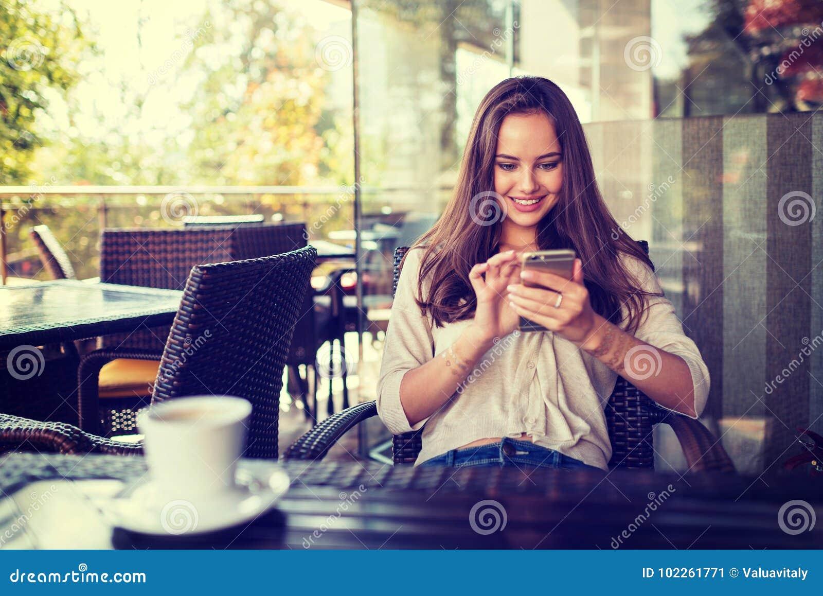 Kobieta w kawiarni pić kawowy i używać jej telefon komórkowego