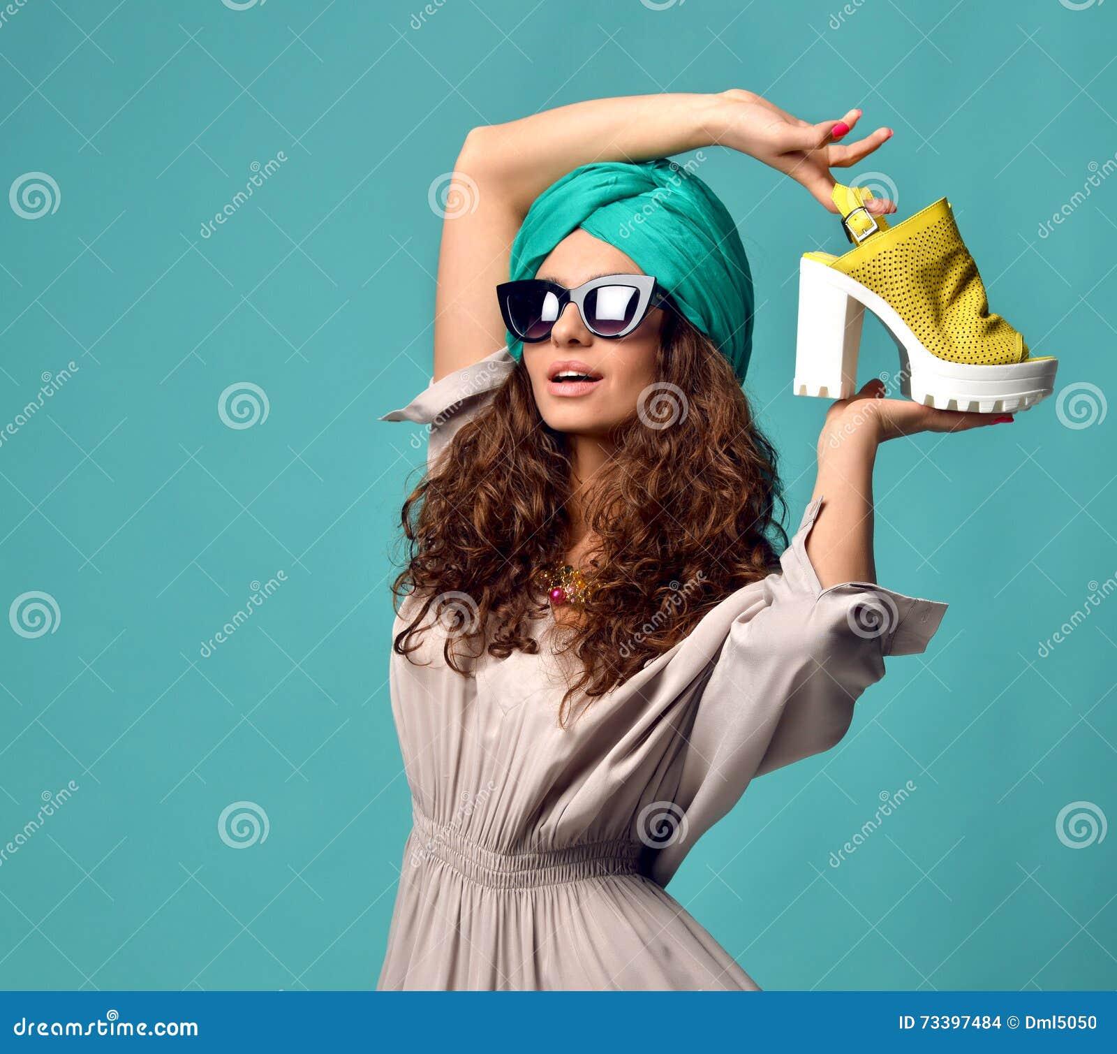 Kobieta w nowożytnych kotów oczu okularach przeciwsłonecznych z białym koloru żółtego butem