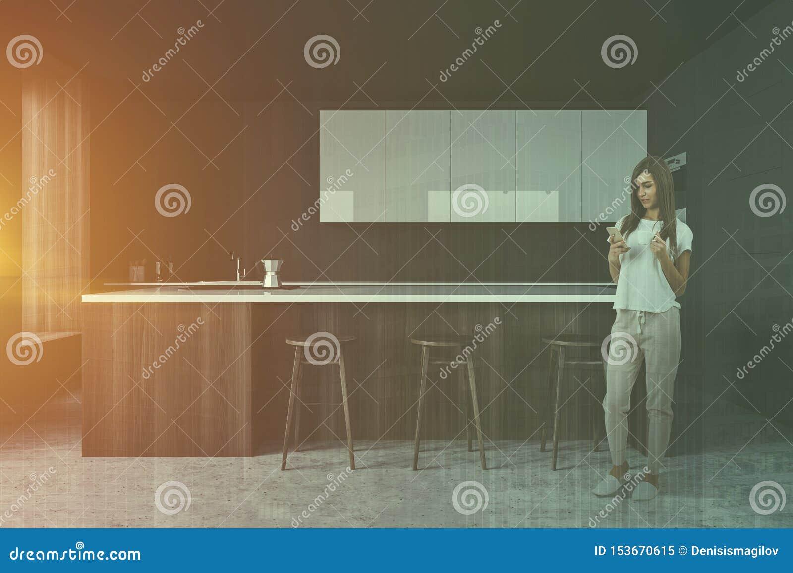 Kobieta w szarej kuchni z barem
